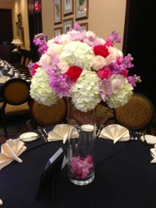 Tall arrangements of hydrangea, roses, stock, chrysanthemum with petals at the bottom of the cylinders.